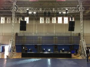 """In April 2013 we provided a complete, turn key production for People of the Beat. The event was held in Bender Arena at American University in Washington, DC. We built a 40' span by 30' high self climbing goal post structure using 30"""" heavy duty PRT box truss for the span, and 12'' box truss for each vertical tower. Rigged to the span were (2) CM 1-ton chain motors, (8) EAW kf650 virtual line array cabinets, (6) Martin MAC 2000 profile intelligent fixtures, and (2) 1,200watt Cyberlight scanners. The entire rig was raised using two CM 1-ton chain motors. On the ground were (8) double 18"""", B & C loaded, Zann Thug sub woofers totaling 22,400 watts, along with (4) JBL SRX715 front fill speakers. An additional (4) Martin MAC 2000 intelligent lights were placed on the subs. Finally, we had (3) follow spot lights on the job, and wireless communication for the entire production crew. We were limited to a six hour set-up, and were ready ahead of schedule. The production went off without a hitch, and the crew slept well after the 22 hour day."""
