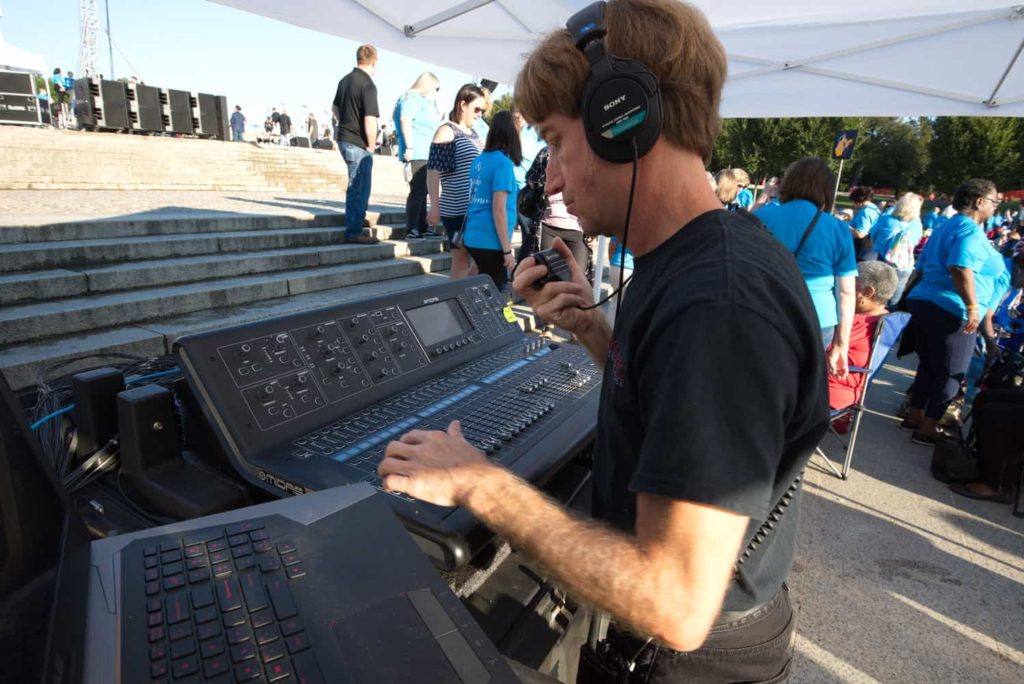 an A1 audio technician checking EQ levels on a digital mixing console during a soundcheck at and event.