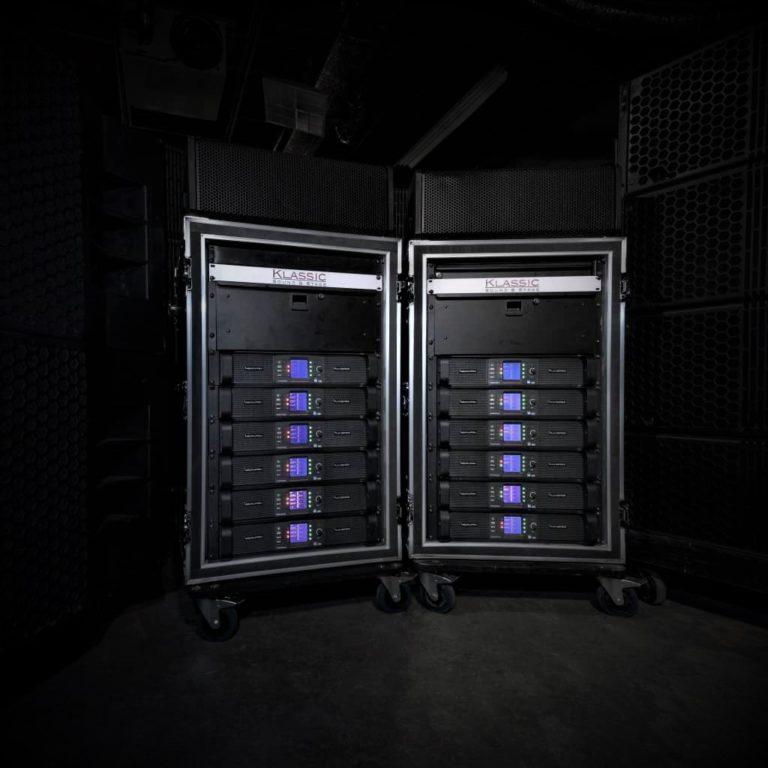 epic shot of line array speakers sitting behind the digital amplifiers and digital audio processing racks.