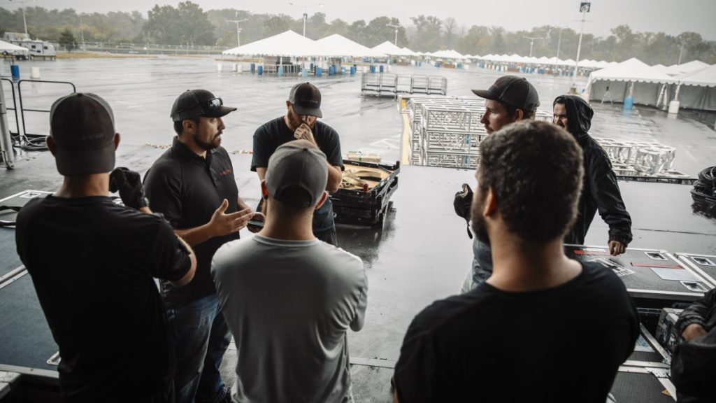 Event crew gathers to listen to instructions from their crew leader, before setting up for an outdoor event.