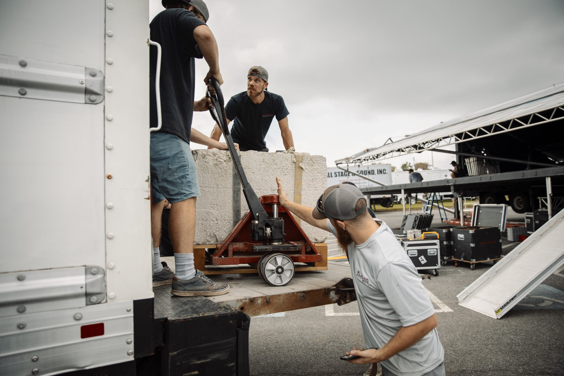 event staff unloads concrete ballast from the box truck