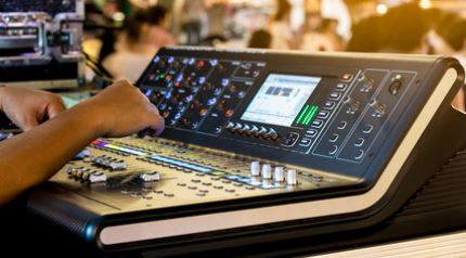 tweaking the EQ of a digital mixing console at a live event