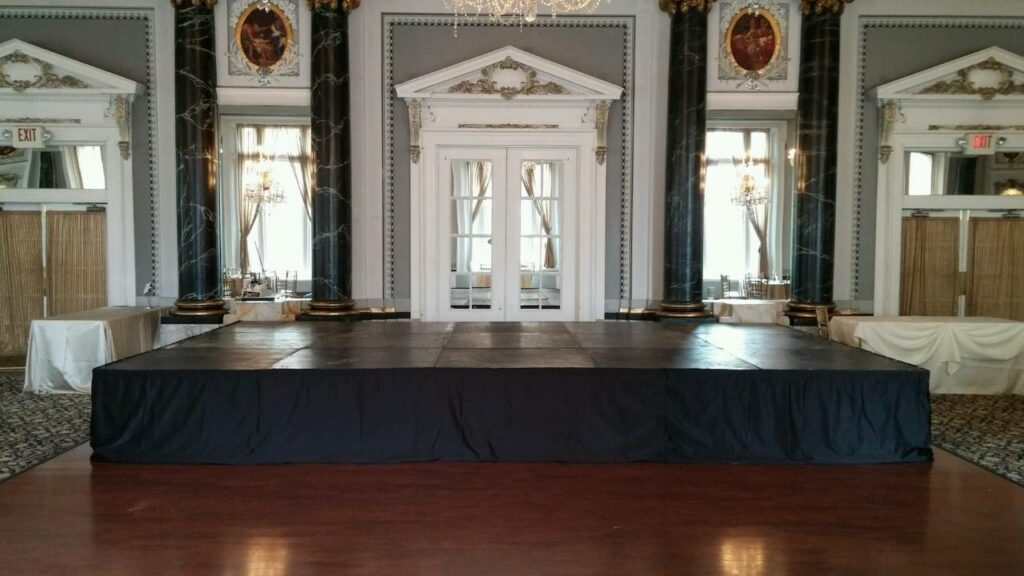 small indoor stage set-up in front of dance floor for a wedding reception