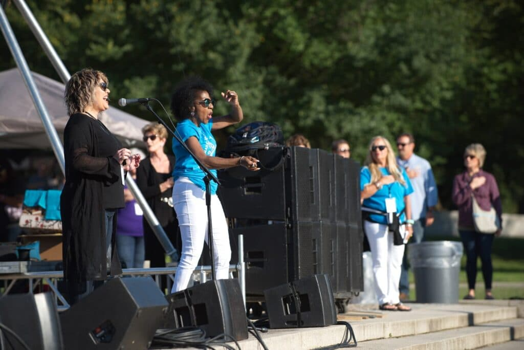 a women sings the national anthem into a microphone on stage at the lincoln memorial