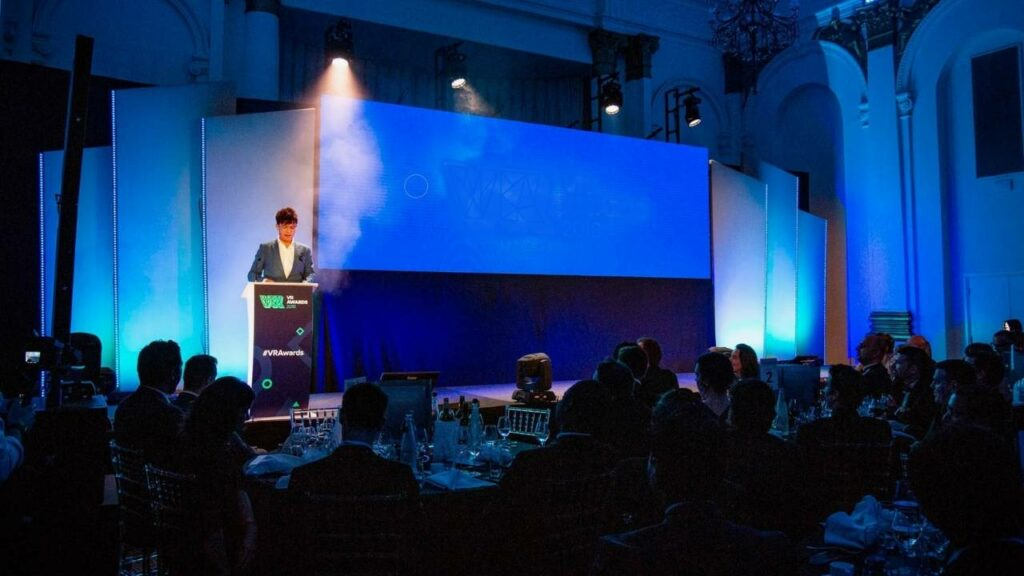 Speaking at a podium during a conference with an LED Video wall backdrop.