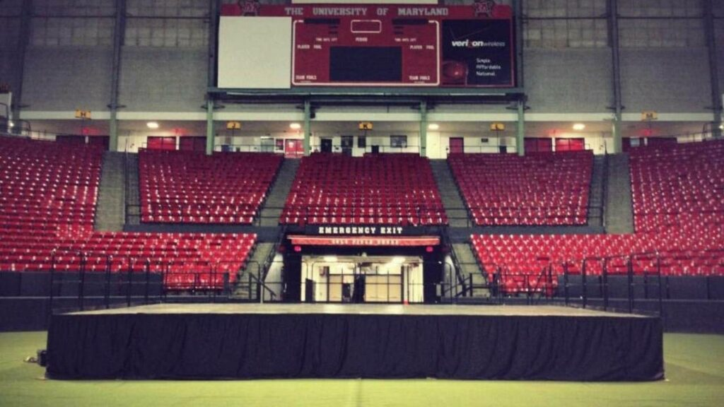 Portable modular stage set-up inside of university arena.