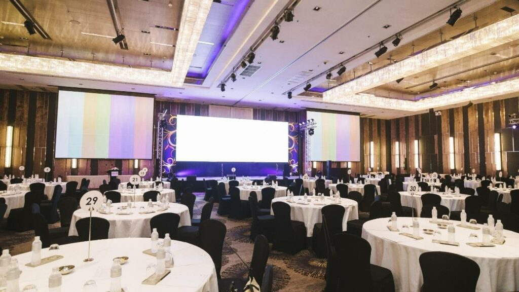 Bright LED video wall screen being used as a backdrop to a small stage riser at a private event in the hotel ballroom.