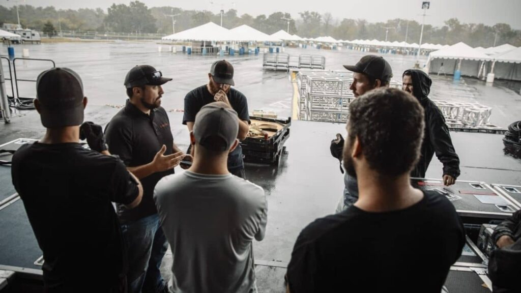 the Production crew leader gathers the technicians to discuss the plan for the day