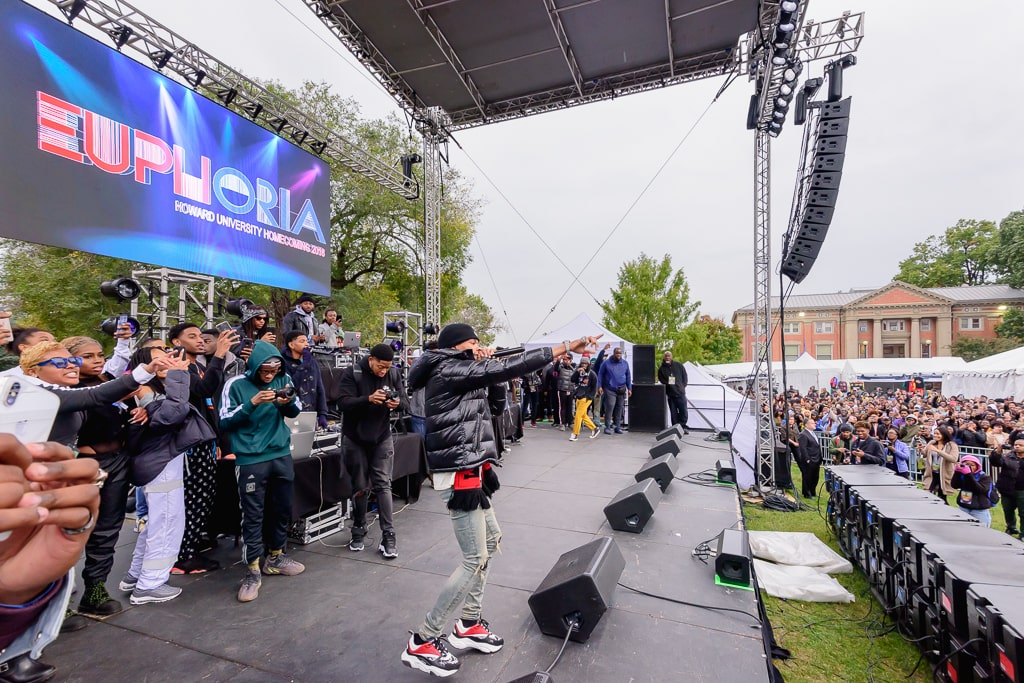 University Homecoming concert with rapper on stage performing to large crowd