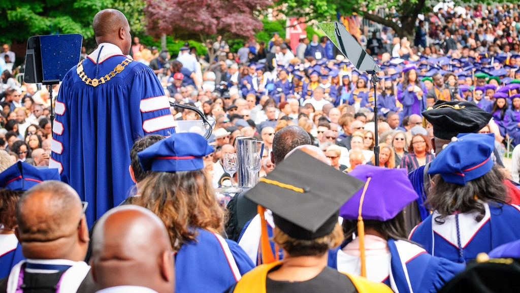 University professors speaks at a podium during Washington DC college commencement ceremony.