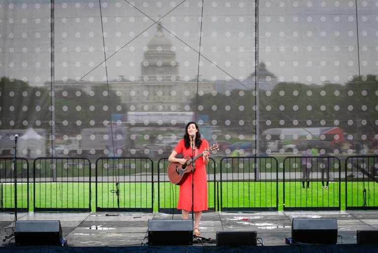 A singer performs on stage during a rally on the National Mall in Washington DC. The United State Capital building is in the background.
