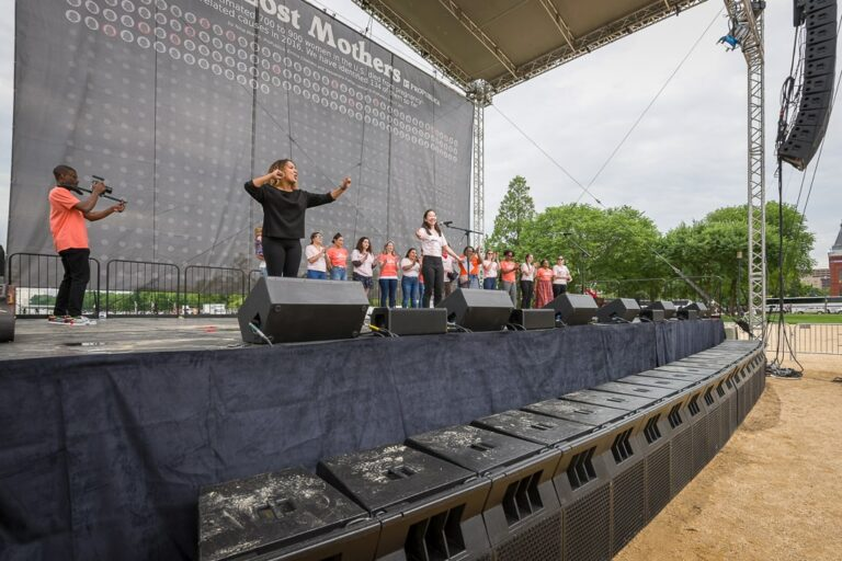 a group performs on stage with a large sound system