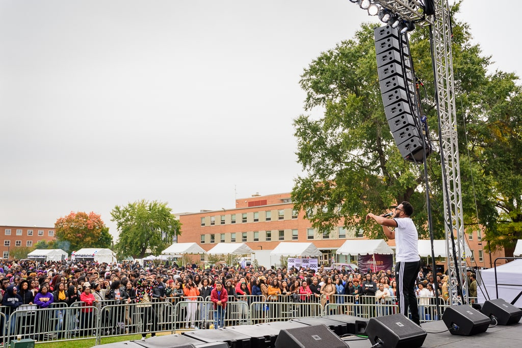 Our line array speakers hanging above a large crowd that is watching a stage performance at a college in Washington DC