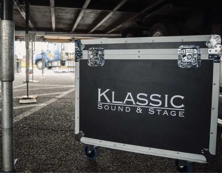 AV road case sitting under a stage while team is setting up for an outdoor concert.